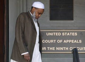 Photo - FILE - This May 11, 2012 file photo, Portland Imam Mohamed Sheikh Abdirahman Kariye, who is one of 15 men who say their rights were violated because they are on the U.S. government's no-fly list, leaves the United Sates Court of Appeals following oral arguments on the ACLU No Fly List challenge, in Portland, Ore. A federal judge has ruled Tuesday, June 24, 2014, that the U.S. government violated the rights of 13 people on its no-fly list by depriving them of their constitutional right to travel, and gave them no adequate way to challenge their placement on the list. (AP Photo/Rick Bowmer, File)