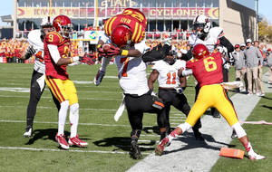 Photo - Iowa State running back DeVondrick Nealy (20) jumps over the top of Oklahoma State safety Shamiel Gary (7) to score a touchdown during the first half of an NCAA college football game in Ames, Iowa Saturday, Oct. 26, 2013.(AP Photo by Justin Hayworth)