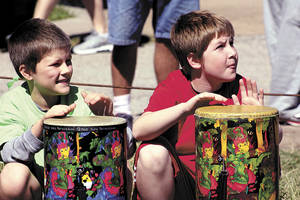 "Photo - Hayden Shumway, left, and Connor Thomason, of Monroe Elementary School, play African drums in a multi-school band called Manyawi, an African word meaning ""Let's Go."" The band played Sunday at the start of the annual CROP Walk to Stop Hunger. PHOTO BY LYNETTE LOBBAN, FOR THE OKLAHOMAN"