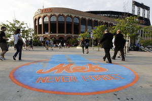 Photo - Fans pass a chalk drawing  in memory of the Sept. 11, terrorist attacks as they approach Citi Field before a baseball game between the New York Mets and the Washington Nationals, Wednesday, Sept. 11, 2013, in New York. (AP Photo/Frank Franklin II)