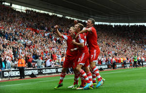 Photo - Southampton's Jose Fonte (not seen) is mobbed by his teammates after he scored his team's equalizer during their Premier League match against Sunderland at St Mary's stadium, Southampton, Saturday, Aug. 24, 2013. (AP Photo/Clive Gee, PA Wire)   UNITED KINGDOM OUT  NO SALES  NO ARCHIVES