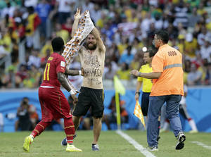 Photo - Ghana's Sulley Muntari helps to assist a man from the pitch after he ran on during the group G World Cup soccer match between Germany and Ghana at the Arena Castelao in Fortaleza, Brazil, Saturday, June 21, 2014. (AP Photo/Matthias Schrader)