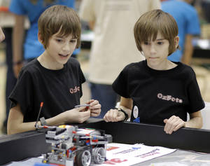 "Photo - ""Ozbots"", a family competing on their own from Norman, 10 year old Identical twins Luke, left, and Aiden Ozment  make adjustments to their robot as they compete at the Nature's Fury Challenge, state championship for the Jr. First Lego League at Santa Fe high school in Edmond, Saturday, February 22, 2014. Photo by Doug Hoke, The Oklahoman"