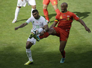 Photo - Algeria's El Arbi Hillel Soudani, left, and Belgium's Vincent Kompany fight for the ball during the group H World Cup soccer match between Belgium and Algeria at the Mineirao Stadium in Belo Horizonte, Brazil, Tuesday, June 17, 2014. (AP Photo/Sergei Grits)