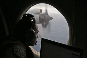 Photo - FILE - In this March 22, 2014 file photo, flight officer Rayan Gharazeddine on board a Royal Australian Air Force AP-3C Orion, searches for the missing Malaysia Airlines Flight MH370 in southern Indian Ocean, Australia.  From the disappearances of aviator Amelia Earhart to labor union leader Jimmy Hoffa, there's just something about a good mystery that Americans find too tantalizing to resist. Perhaps that's why the saga of missing Malaysia Airlines Flight 370 has continued to rivet the country long after people elsewhere have moved on. (AP Photo/Rob Griffith, File)