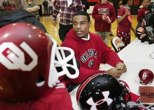 Photo - Dewar defensive back Ronell Lewis was the center of attention after he signed letter of intent to play football at the University of Oklahoma during a school-wide assembly in the school's gym Wednesday morning, February 4, 2009. For nearly an hour after he inked the letter, he was still in the gym sugning autographs, shaking hands and posing for pictures with fans that ranged from babies to retired townspeople. BY JIM BECKEL