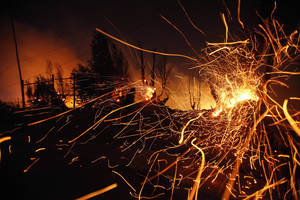 Photo - Sparks fly carried by the wind as a large forest fire reaches urban areas in Valparaiso, Chile, Sunday April 13, 2014. Authorities say the fires have destroyed hundreds of homes, forced the evacuation of thousands and claimed the lives of at least seven people.  ( AP Photo/ Luis Hidalgo)