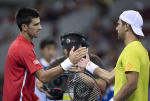 Photo -   Serbia's Novak Djokovic, left, shakes hands with Jurgen Melzer of Austria after their men's singles quarterfinal match of the China Open tennis tournament in Beijing Friday, Oct. 5, 2012. Djokovic defeated Melzer 6-1, 6-2. (AP Photo/Andy Wong)