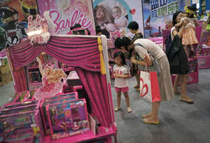 Photo - FILE - In this Thursday, July 25, 2013, file photo, women with their children visit Barbie toys on display for sale at the Kids Fun Expo in Beijing.  Mattel, which manufactures Barbie toys, reports quarterly earnings on Oct. 16, 2013. (AP Photo/Andy Wong, File)