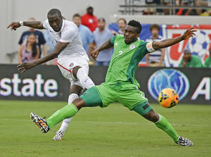 Photo - United States's Jozy Altidore, left, scores a goal as he kicks the ball past Nigeria's Joseph Yobo, right, during the second half of an international friendly soccer match in Jacksonville, Fla., Saturday, June 7, 2014. The United States won 2-1. (AP Photo/John Raoux)