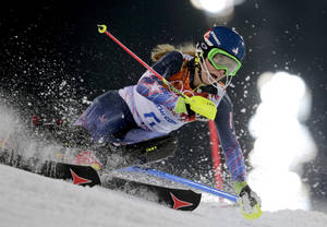 Photo - Gold medal winner Mikaela Shiffrin skis past a gate in the women's slalom at the Sochi 2014 Winter Olympics, Friday, Feb. 21, 2014, in Krasnaya Polyana, Russia. (AP Photo/Charles Krupa)