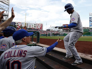 Photo - New York Mets' Juan Lagares, right, celebrates with manager Terry Collins (10) and others after his two-run homer during the third inning of a baseball game against the Washington Nationals at Nationals Park Saturday, May 17, 2014, in Washington. (AP Photo/Alex Brandon)