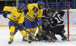 Photo - Erika Grahm and Jenni Asserholt of Sweden battle Goalkeeper Nana Fujimoto and Haruna Yoneyama of Japan, (L-R) in front of the net during the 2014 Winter Olympics women's ice hockey game at Shayba Arena, Sunday, Feb. 9, 2014, in Sochi, Russia. (AP Photo/Petr David Josek)