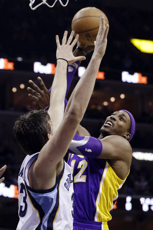 Photo - Los Angeles Lakers' Dwight Howard (12) goes to the basket over Memphis Grizzlies' Marc Gasol (33), of Spain, during the first half of an NBA basketball game in Memphis, Tenn., Wednesday, Jan. 23, 2013. (AP Photo/Daniel Johnston)