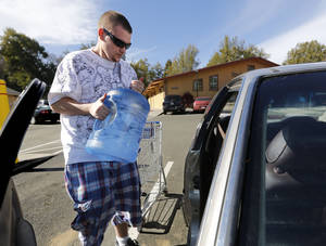 Photo - FILE - In this Feb. 4, 2014 file photo, Forrest Clark loads five-gallon bottles of water purchased at a local store into his car in Willits, Calif. State public health officials have reduced the number of communities at risk of losing their drinking water due to California's drought from 17 to three. In the Mendocino County town of Willits, which was two months from losing its drinking water, well drilling efforts and rain have helped officials ease restrictions. (AP Photo/Rich Pedroncelli, file)