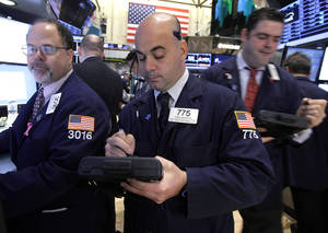photo - FILE- In this Thursday, Dec. 6, 2012, file photo, Trader Fred DeMarco, center works on the floor of the New York Stock Exchange. World stock markets swung higher Friday Dec. 14, 2012 after a survey showed an improvement in China&#039;s manufacturing, offsetting gloom from a sharp drop in Japanese business confidence. (AP Photo/Richard Drew, File)