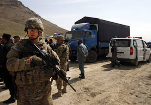 photo - A U.S. soldier secures the scene after U.S. forces shot on an Afghan truck, center, killing two passengers and injuring another on the road between Kabul and Bagram, Afghanistan, Monday, March 11, 2013. (AP Photo/Ahmad Jamshid)