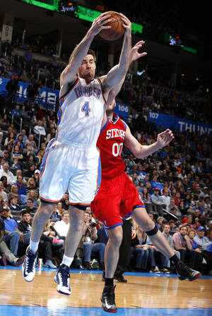 photo - Oklahoma City's Nick Collison (4) grabs a rebound from Philadelphia's Spencer Hawes (00) during the NBA game between the Oklahoma City Thunder and the Philadelphia 76ers at the Chesapeake Energy Arena in Oklahoma City, Friday,Jan. 4, 2013. Photo by Sarah Phipps, The Oklahoman