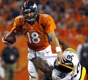 Photo -   Denver Broncos quarterback Peyton Manning (18) is wrapped up by Pittsburgh Steelers linebacker Larry Foote (50) during the second quarter of an NFL football game, Sunday, Sept. 9, 2012, in Denver. (AP Photo/David Zalubowski)