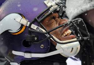 Photo - Minnesota Vikings running back Adrian Peterson reacts as he is tended to after injuring his ankle on a play in the second quarter of an NFL football game against the Baltimore Ravens, Sunday, Dec. 8, 2013, in Baltimore. (AP Photo/Gail Burton)