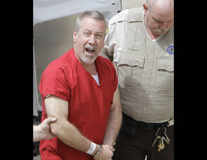Photo -   FILE - In this May 8, 2009 file photo, former Bolingbrook, Ill., police sergeant Drew Peterson yells to reporters as he arrives at the Will County Courthouse in Joliet, Ill., for his arraignment on charges of first-degree murder in the 2004 death of his former wife Kathleen Savio. A jury on Thursday, Sept. 6, 2012, found Peterson guilty of murdering his third wife. (AP Photo/M. Spencer Green, File)