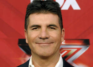"Photo - FILE - In this Dec. 22, 2011, file photo, television personality Simon Cowell poses on the red carpet at The X Factor Finale show in Los Angeles.  Simon Cowell said Monday, Dec. 16, 2013, he is plotting changes for ""The X Factor,"" including new judges and a new role for him.(AP Photo/Dan Steinberg)"