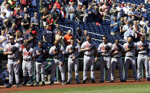 Photo - The Atlanta Braves observe a moment of silence before a baseball game against the Washington Nationals at Nationals Park Tuesday, Sept. 17, 2013, in Washington, to honor those killed and injured in Monday's attack at the nearby Washington Navy Yard. (AP Photo/Alex Brandon)