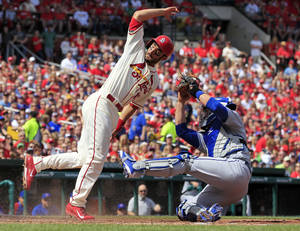 Photo - St. Louis Cardinals' Matt Carpenter, left, scores as he avoids the tag from Chicago Cubs catcher John Baker during the fourth inning of a baseball game Saturday, April 12, 2014, in St. Louis. (AP Photo/Jeff Roberson)