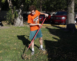 Photo - Bishop McGuinness senior Casey Burnstein rakes leaves as part of a community service project at The Sanctuary women's development center, 2133 SW 11 in Oklahoma City.  <strong>SARAH PHIPPS - SARAH PHIPPS</strong>