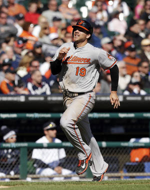Photo - Baltimore Orioles' Chris Davis scores from first on a triple by teammate Adam Jones during the ninth inning of a baseball game against the Detroit Tigers in Detroit, Saturday, April 5, 2014. (AP Photo/Carlos Osorio)