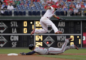Photo - Atlanta Braves' Jordan Schafer steals second as Philadelphia Phillies' Cesar Hernandez top misplays the ball  in the first inning of the second game of a baseball double-header Saturday, June 28, 2014, in Philadelphia.  (AP Photo/H. Rumph Jr)