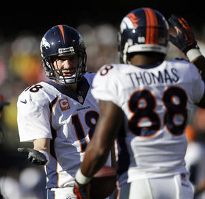 Photo - Denver Broncos quarterback Peyton Manning (18) celebrates with wide receiver Demaryius Thomas (88) after they connected for a 5-yard touchdown against the Oakland Raiders during the second quarter of an NFL football game, Sunday, Dec. 29, 2013, in Oakland, Calif. With that completion, Manning set the all-time single season passing yardage record. (AP Photo/Marcio Jose Sanchez)