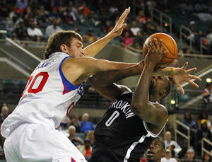 photo -   Brooklyn Nets' Andray Blatche (0) is fouled by Philadelphia 76ers' Spencer Hawes (00) during the second half of an NBA preseason basketball game in Atlantic City, N.J., Saturday, Oct. 13, 2012. The Nets defeated the 76ers 108-105 in overtime. (AP Photo/Rich Schultz)