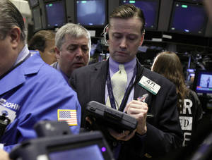 Photo - Neil Catana, right, works with fellow traders on the floor of the New York Stock Exchange. Markets were on edge Friday. AP Photo