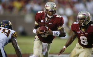 Photo - Florida State quarterback Jameis Winston, center, runs in the second quarter of an NCAA college football game against Bethune-Cookman on Saturday, Sept. 21, 2013, in Tallahassee, Fla. (AP Photo/Phil Sears)