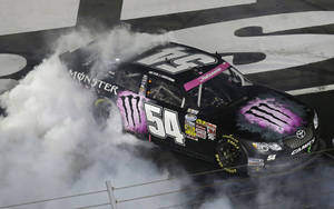 Photo - Kyle Busch does a burnout after winning the NASCAR Nationwide Series auto race at Charlotte Motor Speedway in Concord, N.C., Friday, Oct. 11, 2013. (AP Photo/Gerry Broome)