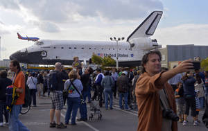 "photo -   Spectators gather around the Space Shuttle Endeavour before it is moved along city streets, Friday, Oct.12, 2012, in Los Angeles. Endeavour's two-day, 12-mile road trip to the California Science Center, where it will be put on display, kicked off early Friday. Rolled on a 160-wheeled carrier, it left from a hangar at the Los Angeles International Airport, passing diamond-shaped ""Shuttle Xing"" signs, and reached city streets about two hours later. (AP Photo/Mark J. Terrill)"