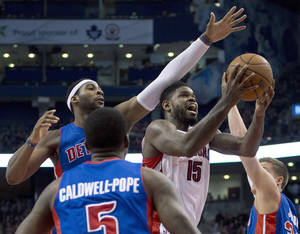 Photo - Toronto Raptors forward Amir Johnson (15) is fouled as he drives throught Detroit Pistons forward Jonas Jerebko (33), center Andre Drummond. left.  and guard Kentavious Caldwell-Pope (5) during first half NBA basketball action in Toronto on Wednesday March 12, 2014. (AP Photo/The Canadian Press, Frank Gunn)