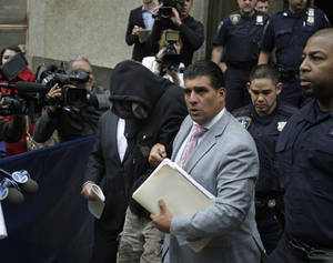 Photo - Wojciech Braszczok, center left, with face covered, leaves the courthouse in New York, Wednesday, Oct. 9, 2013. Braszczok, an undercover police detective, was charged with gang assault in a motorcycle rally that descended into violence in New York. (AP Photo/Seth Wenig)