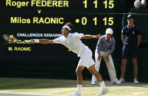 Photo - Roger Federer of Switzerland plays a return to Milos Raonic of Canada during their men's singles semifinal match at the All England Lawn Tennis Championships in Wimbledon, London, Friday, July 4, 2014. (AP Photo/Ben Curtis)