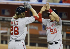 Photo - Washington Nationals' Jayson Werth (28) is met by Jose Lobaton (59) at the plate after they scored on a three-run home run by Werth during the sixth inning of the MLB National League baseball game against the Miami Marlins, Wednesday, April 16, 2014, in Miami. (AP Photo/Lynne Sladky)
