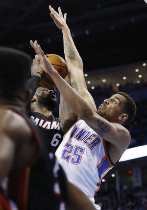 Photo - Miami Heat forward LeBron James (6) is fouled by Oklahoma City Thunder guard Thabo Sefolosha (25) in the second quarter of an NBA basketball game in Oklahoma City, Thursday, Feb. 20, 2014. (AP Photo/Sue Ogrocki)