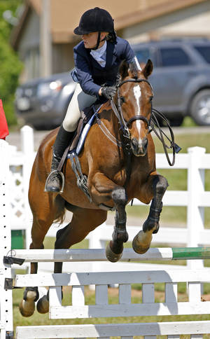 Photo - Above right: Ashley Jumper, riding Cassanova, competes in stadium jumping Saturday during the U.S. Eventing Association's horse trials at Feather Creek Farm.