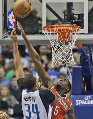 Photo - Dallas Mavericks forward Brandan Wright (34) shoots over Milwaukee Bucks forward Ekpe Udoh (5) during the first half of an NBA basketball game Saturday, Dec. 14, 2013, in Dallas. (AP Photo/LM Otero)
