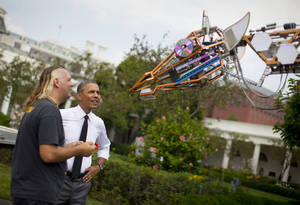 """Photo - President Barack Obama meets Lindsay Lawlor of San Diego, Calif., and his creation, a 17-foot-tall, 2,200-lb robotic giraffe that """"walks"""" on wheels and is powered by a 12-horsepower hybrid fuel-engine motor, during his tour on the South Lawn of the White House in Washington, Wednesday, June 18, 2014,  to meet with students, entrepreneurs and inventors, during the first ever White House """"Maker Faire"""". Obama is highlighting new tools and techniques that promote fledgling businesses create and market their products in an effort to focus attention on US manufacturing need for science and math education. (AP Photo/Pablo Martinez Monsivais)"""