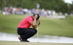 Photo - Tiger Woods bows his head on the fourth green during the final round of the Cadillac Championship golf tournament on Sunday, March 9, 2014, in Doral, Fla. Woods made bogey on the hole. (AP Photo/Lynne Sladky)
