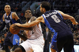 Photo - Phoenix Suns guard Eric Bledsoe (2) draws the foul on Dallas Mavericks guard Jose Calderon (8) in the second half during an NBA basketball game, Saturday, Dec. 21, 2013, in Phoenix. The Suns defeated the Mavericks 123-108. (AP Photo/Rick Scuteri)