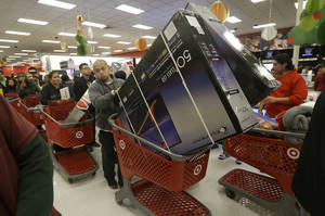Photo - A man pushes two televisions in a shopping cart at a Target store in Colma, Calif., on Thanksgiving Day, Thursday, Nov. 28, 2013. Instead of waiting for Black Friday, which is typically the year's biggest shopping day, more than a dozen major retailers opened on Thanksgiving day this year. (AP Photo/Jeff Chiu)
