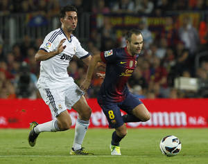 Photo -   Real Madrid's Alvaro Arbeloa, left, in action with FC Barcelona's Andres Iniesta, right, during a Spanish La Liga soccer match at the Camp Nou stadium in Barcelona, Spain, Sunday, Oct. 7, 2012. (AP Photo/Andres Kudacki)
