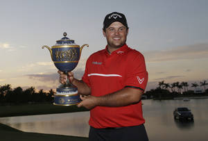 Photo - Patrick Reed holds The Gene Sarazen Cup  after winning the Cadillac Championship golf tournament Sunday, March 9, 2014, in Doral, Fla. (AP Photo/Wilfredo Lee)